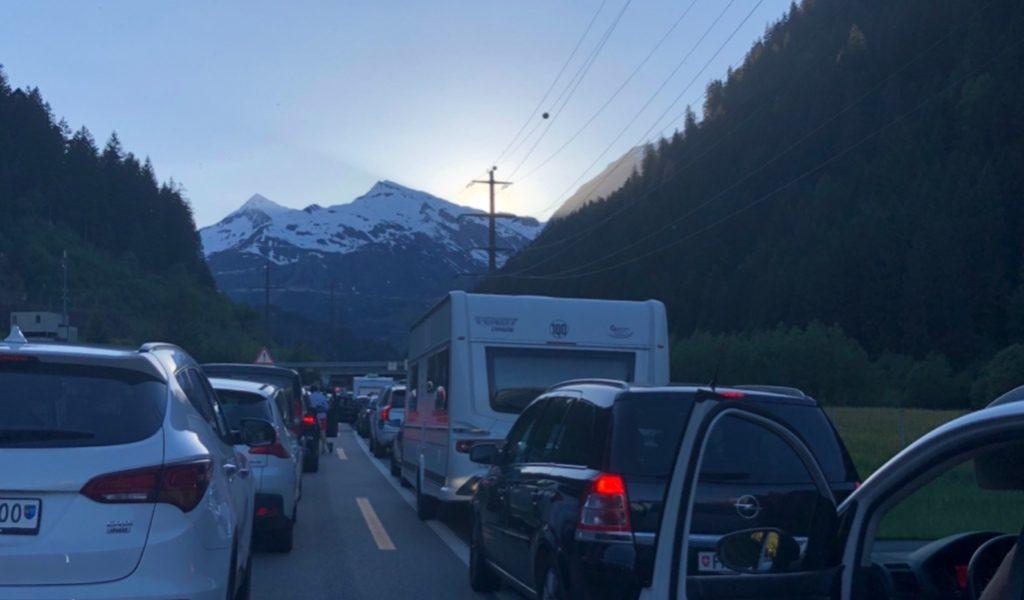 Autos im Stau vor einem Schneebedeckten Berg sind zu sehen, hier ist Warten angesagt.