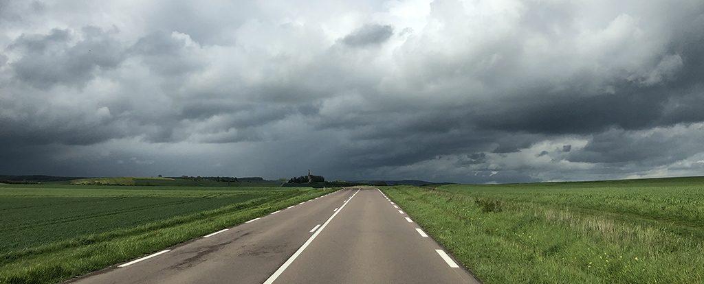 Eine Straße unter schweren Wolken führt bis zum Horizont und steht sinnbildlich für die innere Leere.