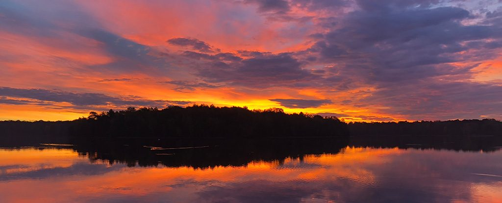 Ein rot glühender Himmel über den Bäumen einer Insel in einem See ist zu sehen. Jeder Sonnenaufgang ist ein Wunder.