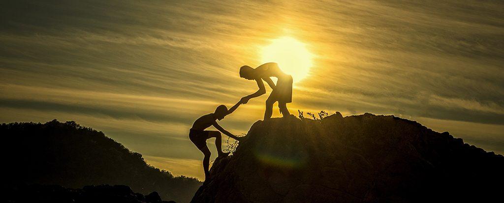 Ein Mensch auf einem Felsen hilft einem zweiten Menschen auf den Felsen zu klettern, dahinter ist die untergehende Sonne sichtbar. Dies verdeutlicht die Idee einer geführten Meditation.