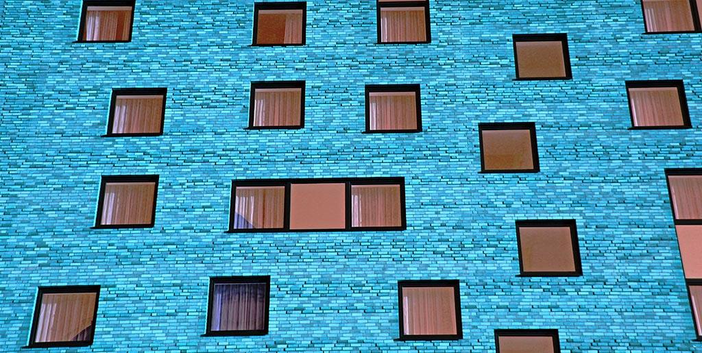 In einer Hauswand mit blauen Klinkern sind viele Fenster, hinter jedem eine eigene Realität.