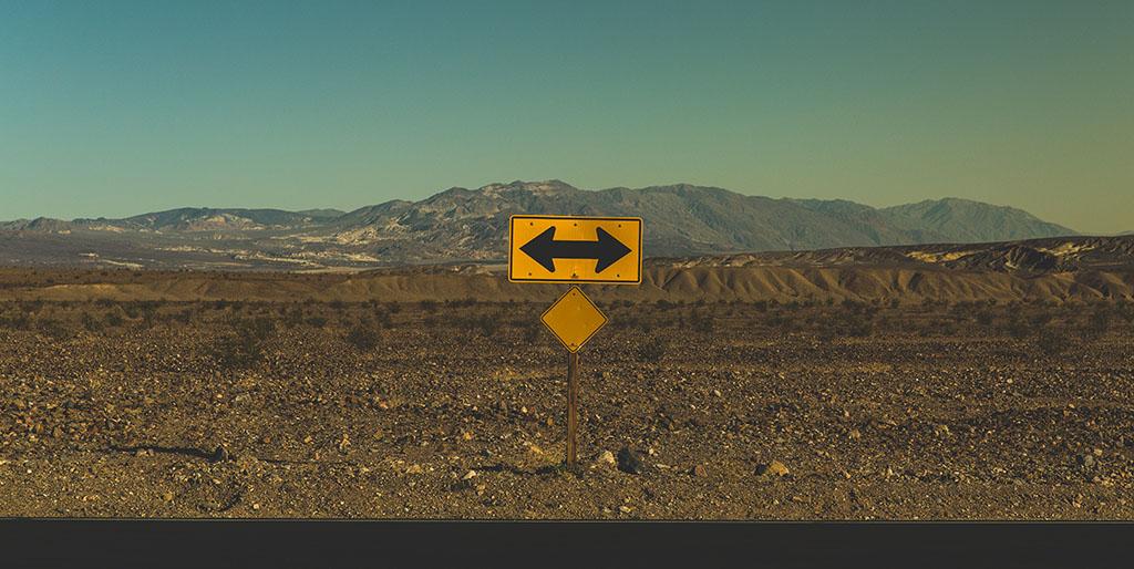 An einer T-Kreuzung in einer kargen Landschaft vor einer Bergkette steht ein Schild mit zwei entgegengesetzten Richtungspfeilen, ein Symbolbild für deinen Blick auf die Zukunft.