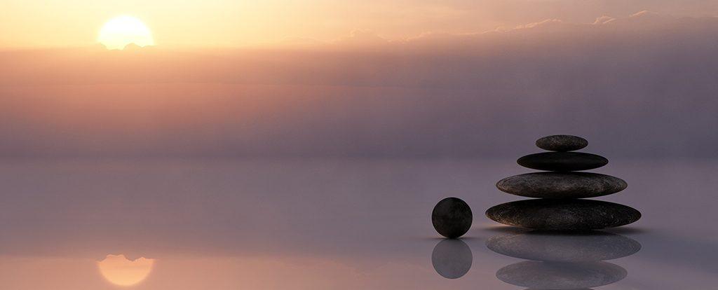 Flache Kiesel liegen in Balance übereinander vor einem Sonnenuntergang.