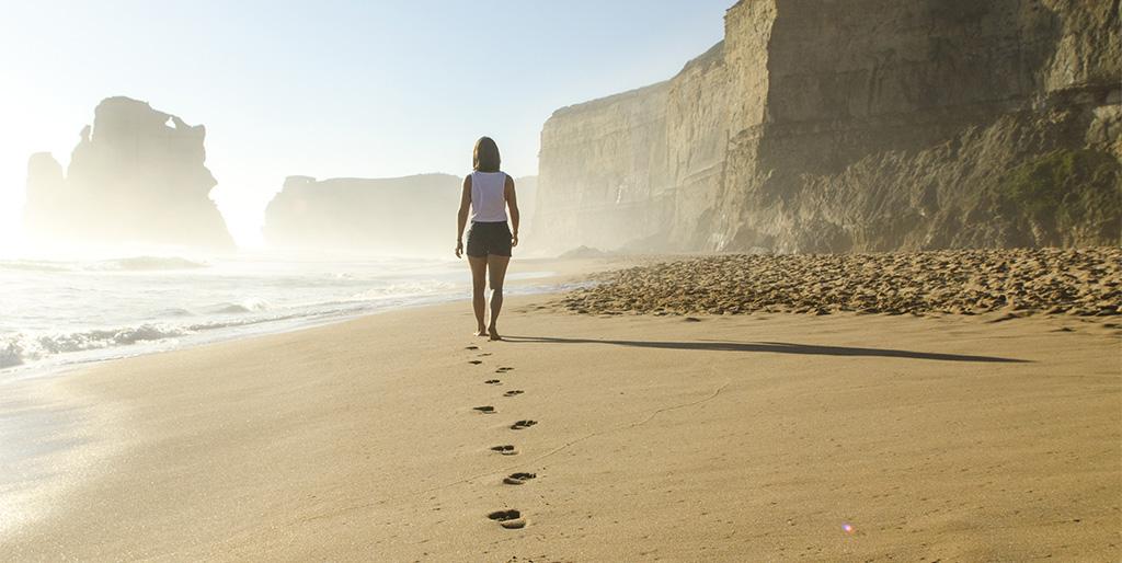 Eine Frau läuft am Strand und hinterlässt Spuren im Sand.