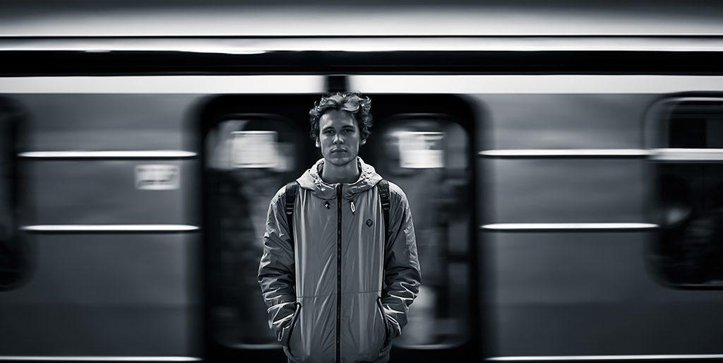 Ein Mann steht vor einem Zug, der im Hintergrund an ihm vorbei fährt.