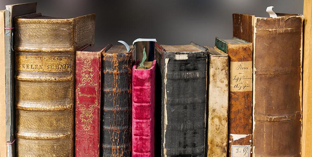 Die Buchrücken alter Bucher sind zu sehen. Sie stehen als Symbol für die Geschichten, die wir uns selber erzählen.