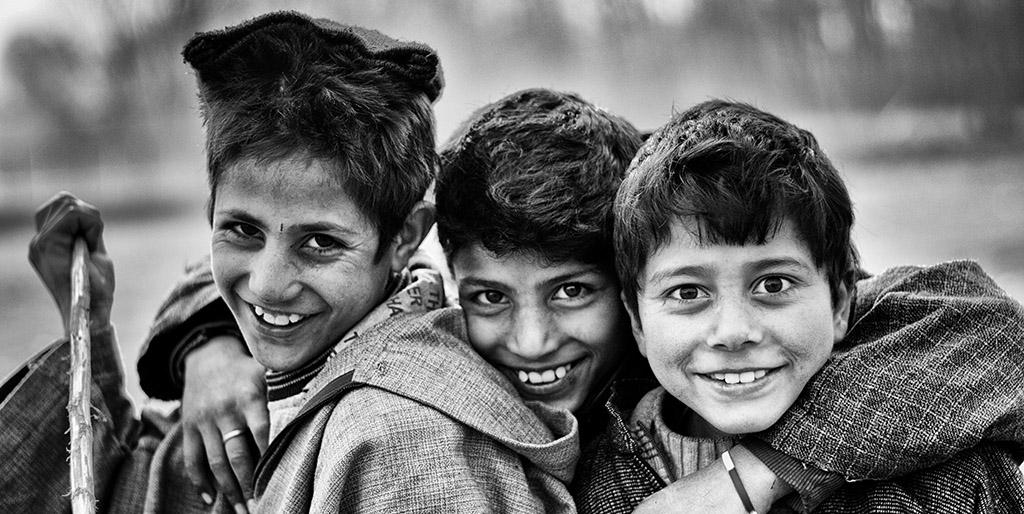 Drei Jungen strahlen in die Kamera, ihre Augen leuchten vor Freude.