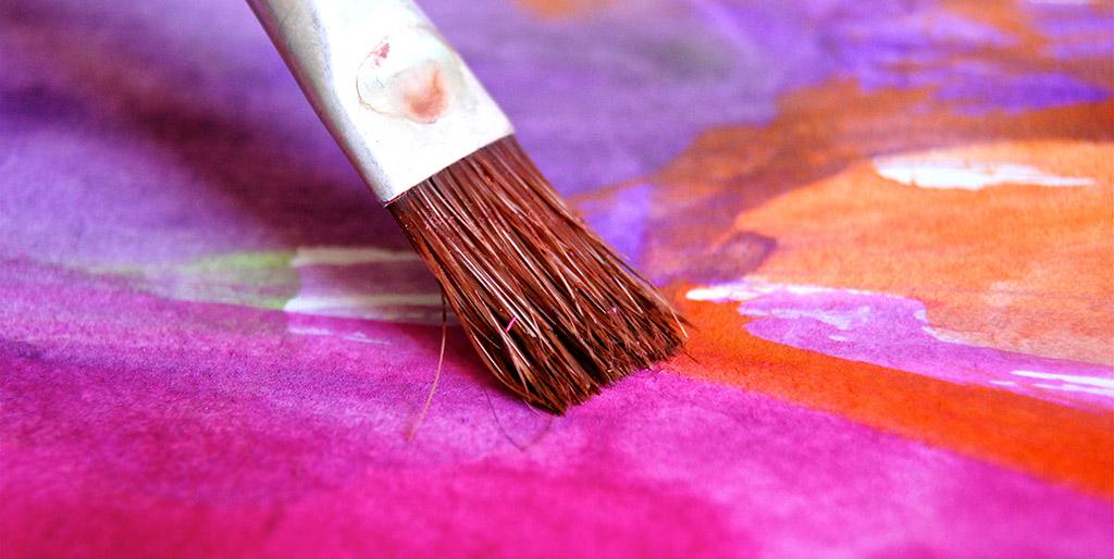 Ein Borstenpinsel malt ein leuchtendes Pink auf ein Bild.