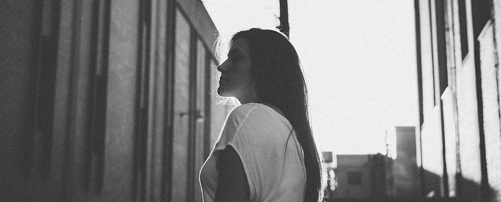 Eine Frau mit dunklen Haaren steht zwischen zwei Gebäuden und atmet ein.