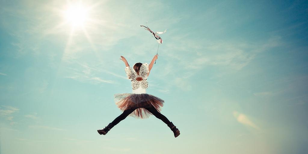 Ein Kind mit Tüllrock, Flügeln und einem Zauberstab springt mit gestreckten Armen und Beinen in die Luft.