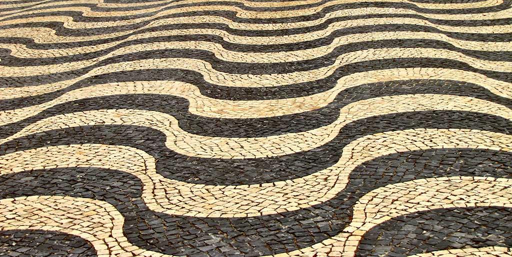 Kleine Steine sind zu einem Pflaster gelegt, das in Wellen verläuft - es verdeutlich die Illusion der Kontrolle.