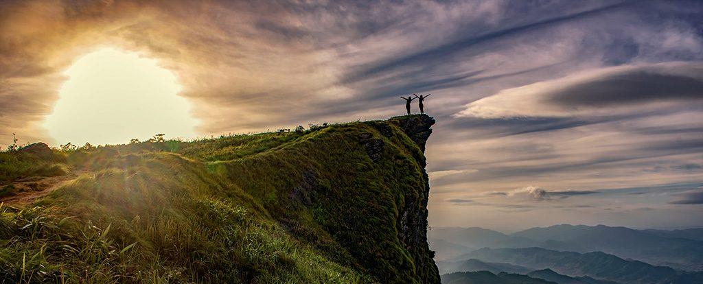 Am Rand einer Klippe stehen zwei Menschen im Sonnenuntergang und genießen ihr Abenteuer.