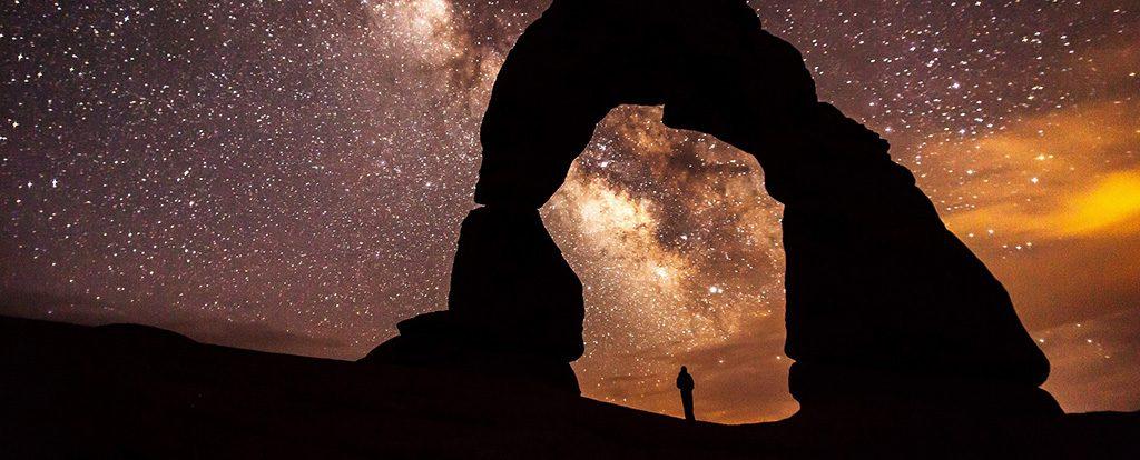 Ein Mensch steht unter einem Bogen aus Stein und über ihm wölbt sich ein Sternenhimmel im letzten Abendlicht.