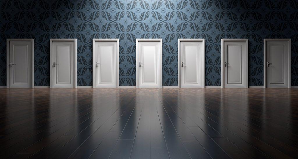 Eine Wand mit sieben weißen Türen ist zu sehen. Eine Entscheidung steht an.