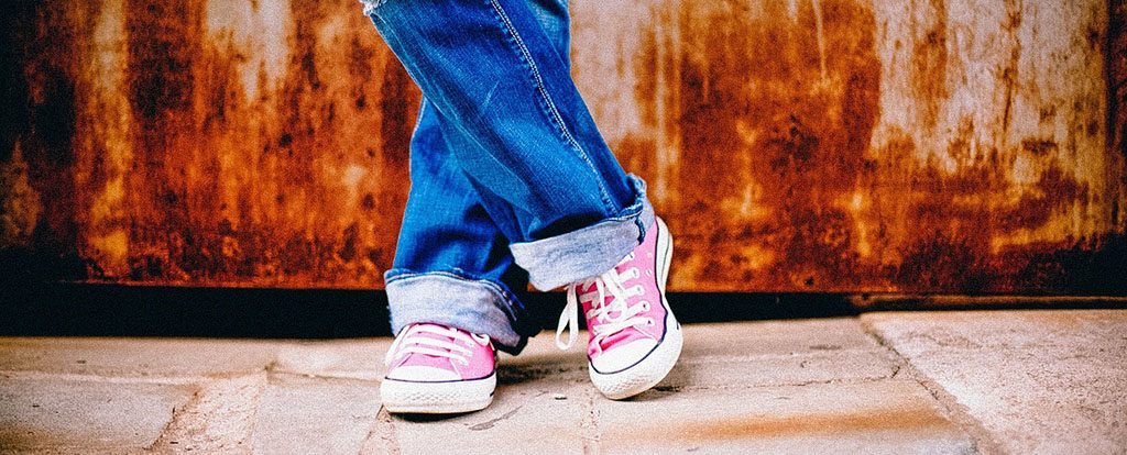 Übereinander geschlagenen Füße sind zu sehen. Bist du in Bewegung oder stehst du still?