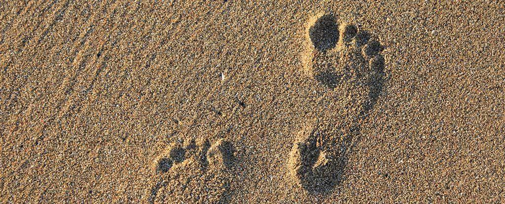 Fußspuren im Sand zeigen den nächsten Schritt.
