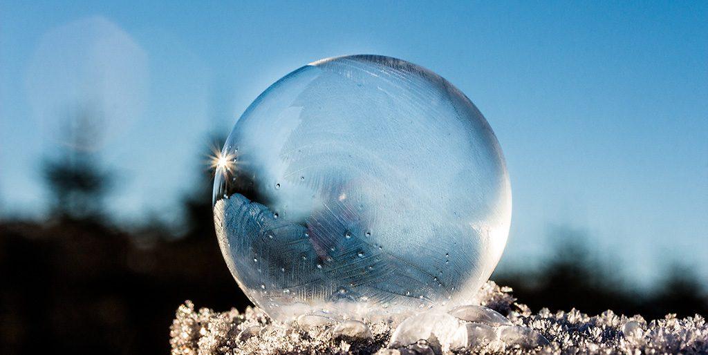 Eine gefrierende Seifenblase im Sonnenlicht steht als Symbol für den Zauber des jetzigen Momentes.