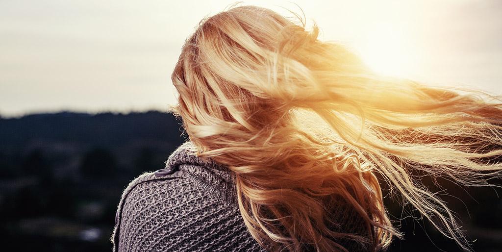Der Wind verweht die Haare einer Frau mit langen blonden Haaren - ein Symbolbild für den Gegenwind des Lebens.