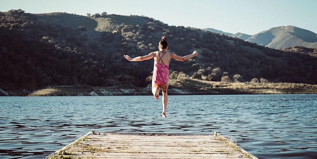 Ein Mädchen in einem rosafarbenen Badeanzug springt voller Lebendigkeit mit ausgebreiteten Armen in einen See.