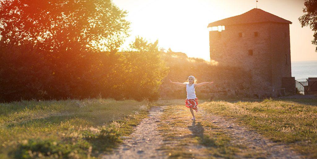 Ein Mädchen läuft mit ausgebreiteten Armen im Abendlicht auf dem Weg vor einem Haus, sie sieht glücklich aus.