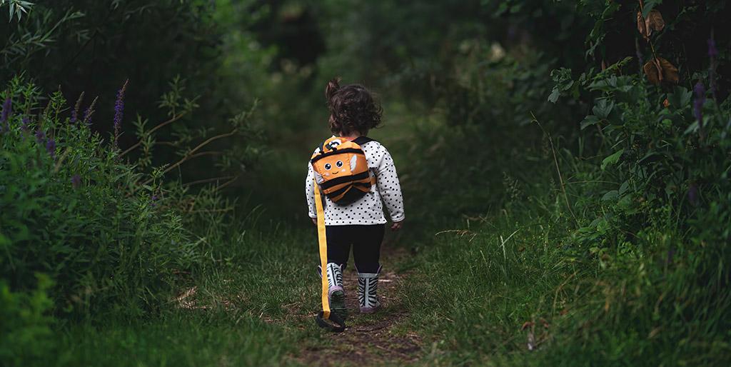 Ein kleines Mädchen mit dunklen Locken und einem orangen Rucksack ist von hinten auf einem schmalen Weg gesäumt mit Büschen.