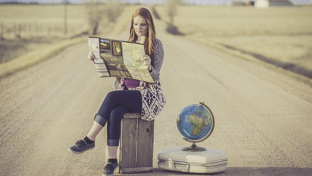 Eine Frau sitzt mit einer Landkarte in der Hand auf einer Kiste, neben ihr liegt ein Koffer auf dem ein Globus steht. Wohin wird ihre Reise gehen?