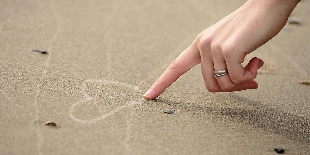 Eine Frauenhand zeichnet ein Herz in den Sand.
