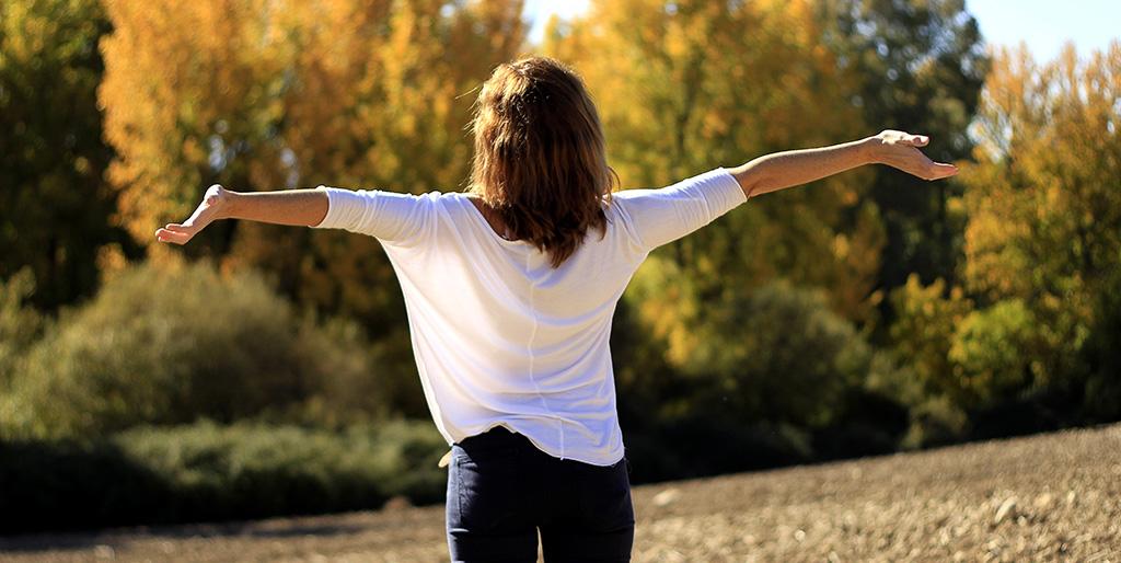 Eine Frau mit ausgebreiteten Armen steht im Sonnenlicht - ein ja oder ein nein zum Leben?
