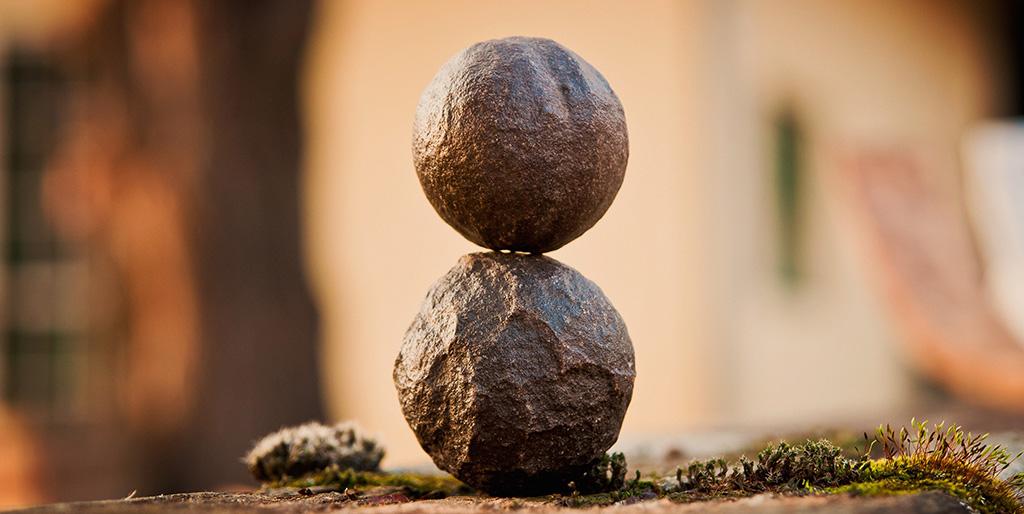 Zwei kugelförmige Steine balancieren aufeinander als Symbol für die Balance im Leben, die mir guttut.