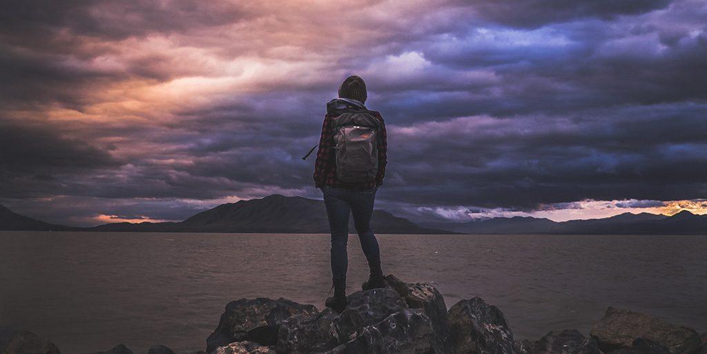 Eine Frau steht mit einem Rucksack auf dem Rücken an einem See wie für einen Neuanfang.
