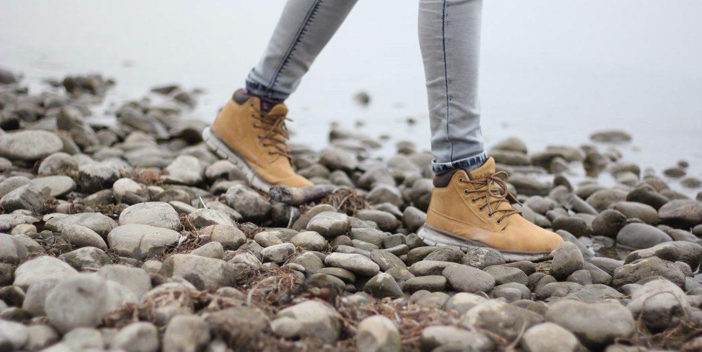 Füße in Wanderschuhen laufen über Kieselsteine als Bild für das Aufraffen und Loslegen.
