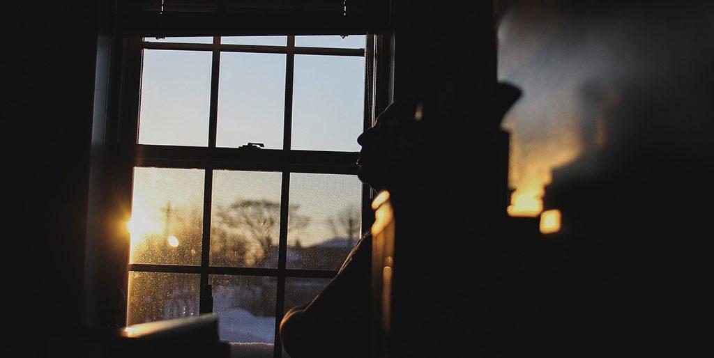 Durch ein Fenster fällt Abendlicht und man sieht die Silhouette eines Mannes, der seinen Gedanken nachhängt.