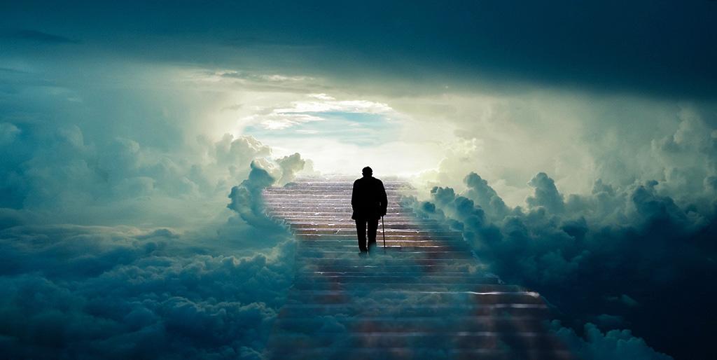 Ein alter Mann mit Stock steigt eine Treppe in den Wolken nach oben - ein Symbolbild für den Weg am Ende des Lebens.