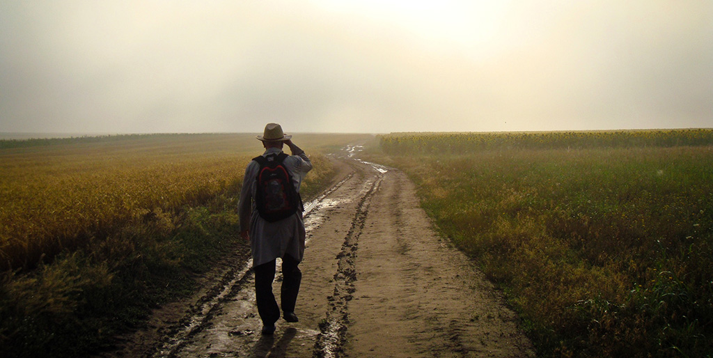 Ein Mann läuft einen Feldweg entlang und fasst sich an seinen Hut - eine Geste des Respekts.