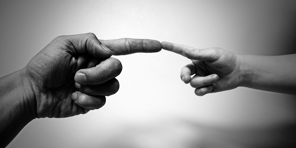 Der Zeigefinger der Hand eines Erwachenen berührt den Zeigefinger eines Kindes, ein Bild für den Dialog mit dem inneren Kind in mir.