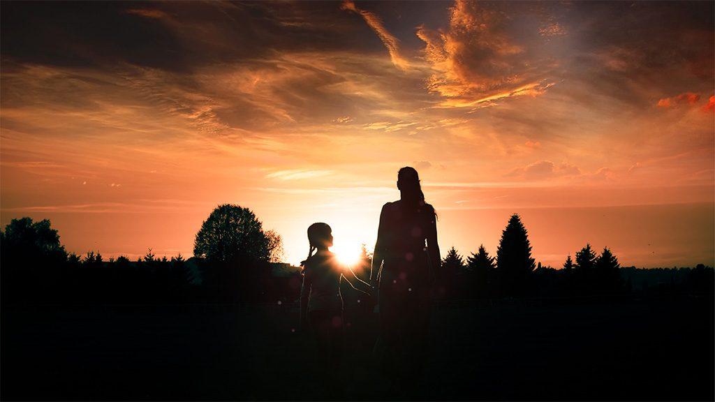 Eine Mutter hat ihr Kind an der Hand und begleitet es in Richtung Sonnenuntergang.