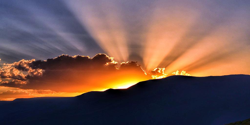 Hinter einem Bergkamm geht die Sonne auf und die Sonnenstrahlen beleuchten den Himmel, ein wunderbarer Tag beginnt.