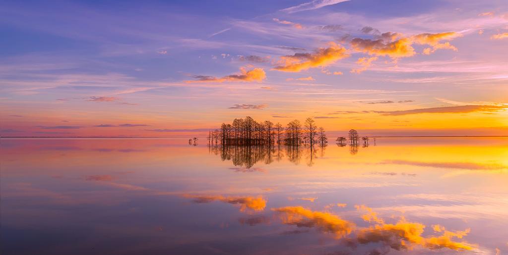 Wolken am Abendhimmel spiegeln sich im glatten Wasser, einzelne Bäume ohne Blätter sind zu sehen.