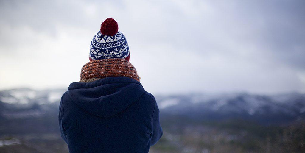 Ein Mensch in Winterjacke und Mütze vor einem nebeligen Bergpanorama ist zu sehen.