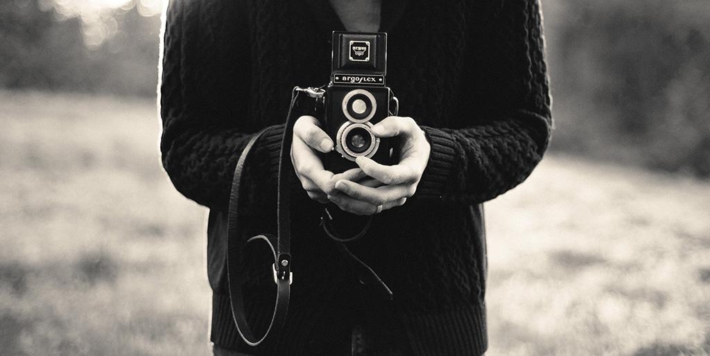 Ein Mann hält eine alte Kamera in der Hand und möchte ein Foto damit machen - wie ein Bild vom Leben.