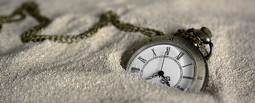 Eine Taschenuhr liegt im Sand als Symbol für das Warten mit seiner Vorfreude.