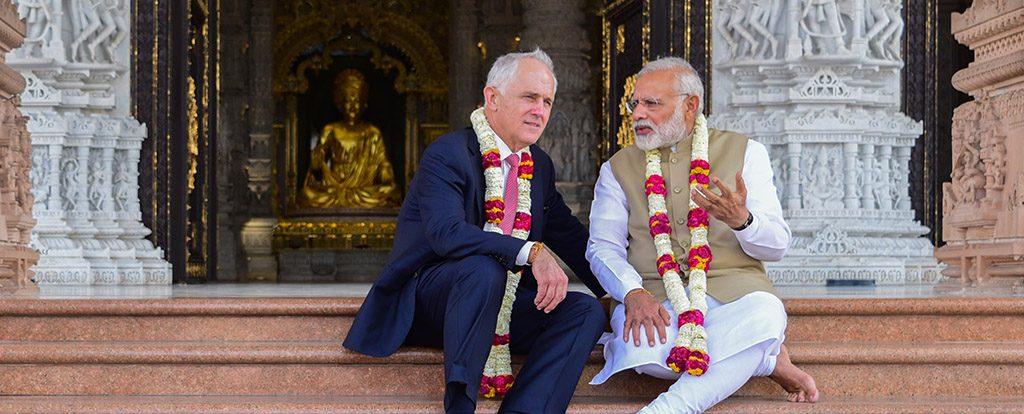 """Ein hiduistischer Gelehrter und ein Mann im Anzug sitzen auf der Treppe vor einem Tempel und unterhalten sich auf Augenhöhe. Hier fragt keiner """"darf ich...""""."""