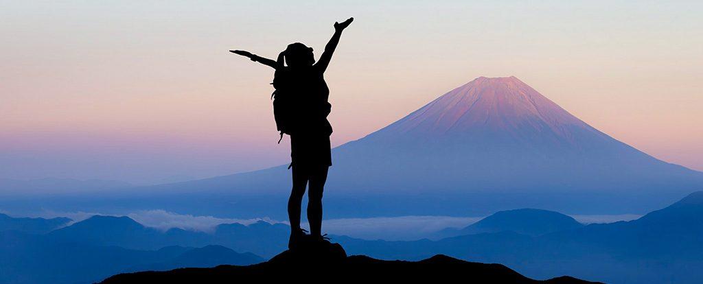 Eine Frau steht auf einem Gipfel mit Blick auf deinen Berg in der Abenddämmerung. Sie streckt die Arme in die Höhe und sagt ja zu ihrem Leben.