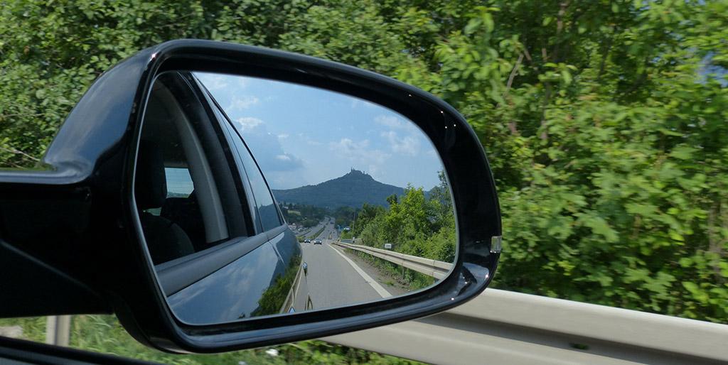 Im Rückspiegel eines Autos ist die hinter uns liegende Straße zu sehen - ein Bild für das Zurückschauen in die Vergangenheit.