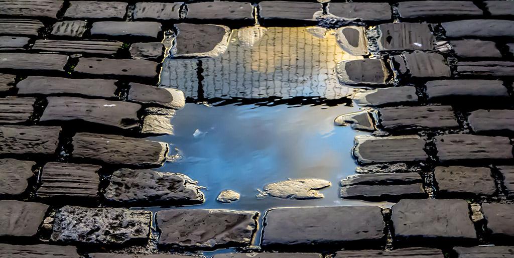 In einer Pfütze auf Kopfsteinpflaster spiegelt sich ein Zaun als Bild meiner inneren Grenzen.