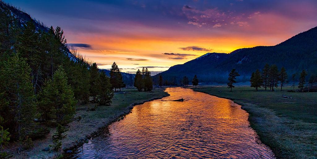 Ein Fluß fließt zwischen Hügeln dem Sonnenuntergang entgegen, das Abendlicht erfüllt den Himmel und spiegelt sich im Wasser.