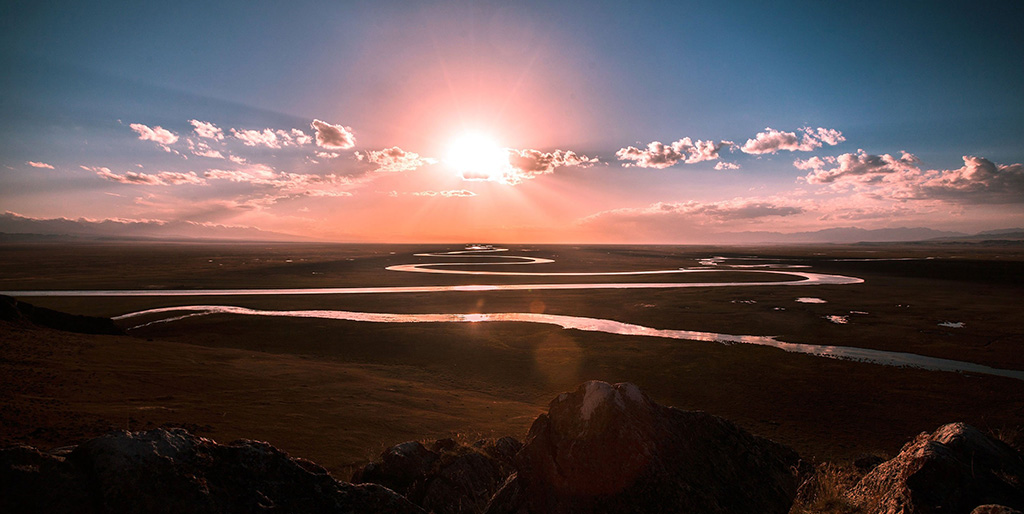 Ein Fluss windet sich vor einer tief stehenden Sonne - so wie Gedanken sich in unserem Kopf winden.