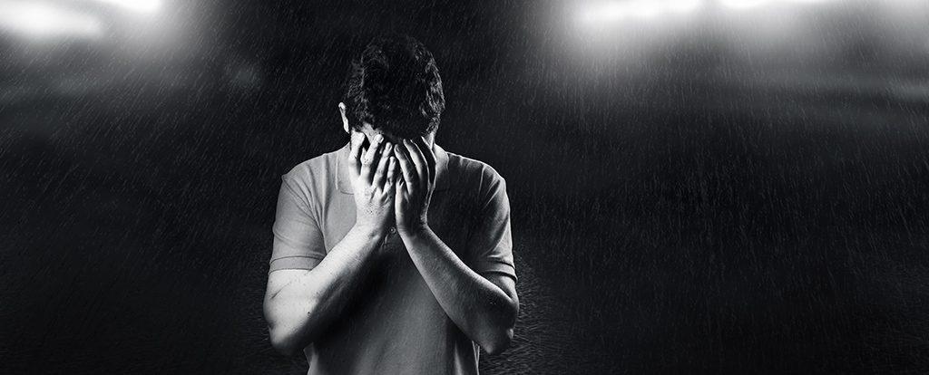 Ein Mann hält sich die Hände vor das Gesicht. Die Enttäuschung ist ihm anzusehen.