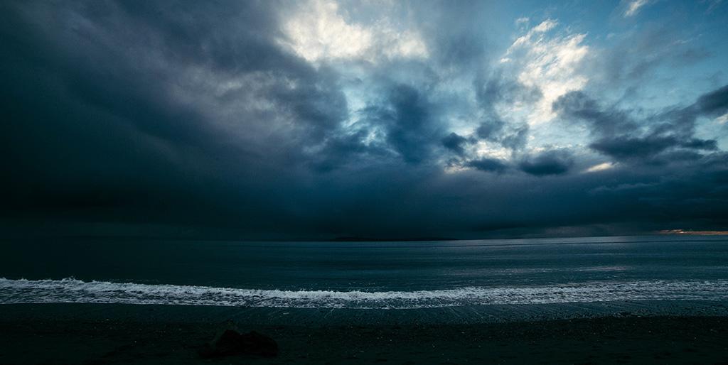 Über der Meeresbrandung ist ein Himmel mit Gewitterwolken zu sehen - ein Bild für eine Krise.