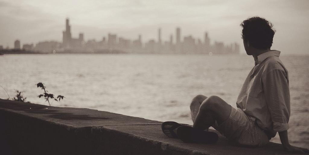 Ein Mann sitzt auf der Kaimauer und schaut auf die Silhouette einer Stadt auf der anderen Seite des Wassers - ein Bild für Warten und Verzicht.